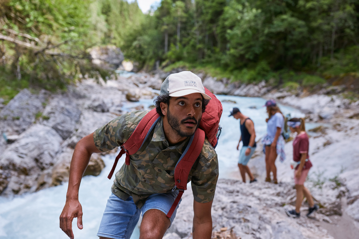 man hiking by river in BUFF hat