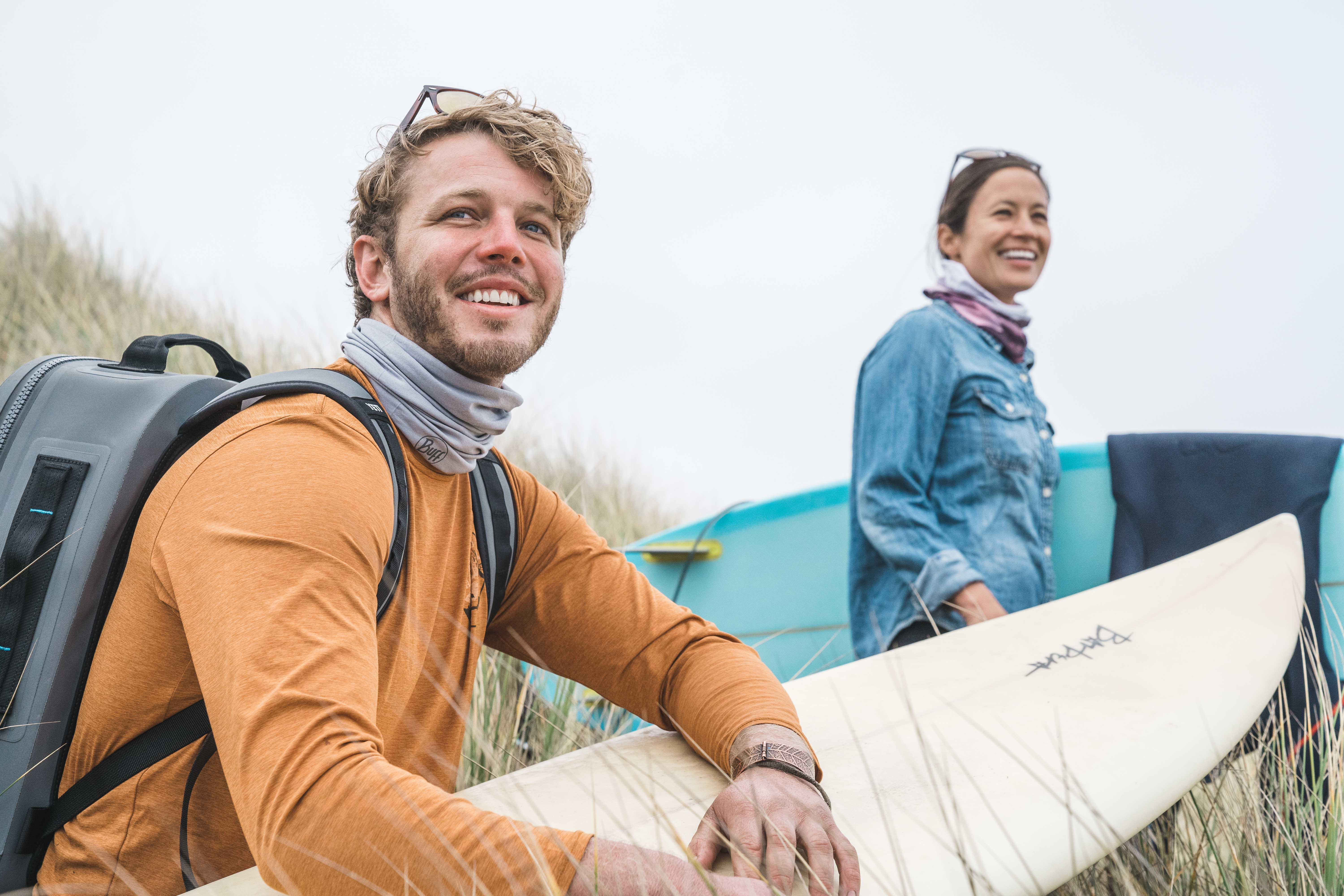 couple arriving at surf spot point at waves