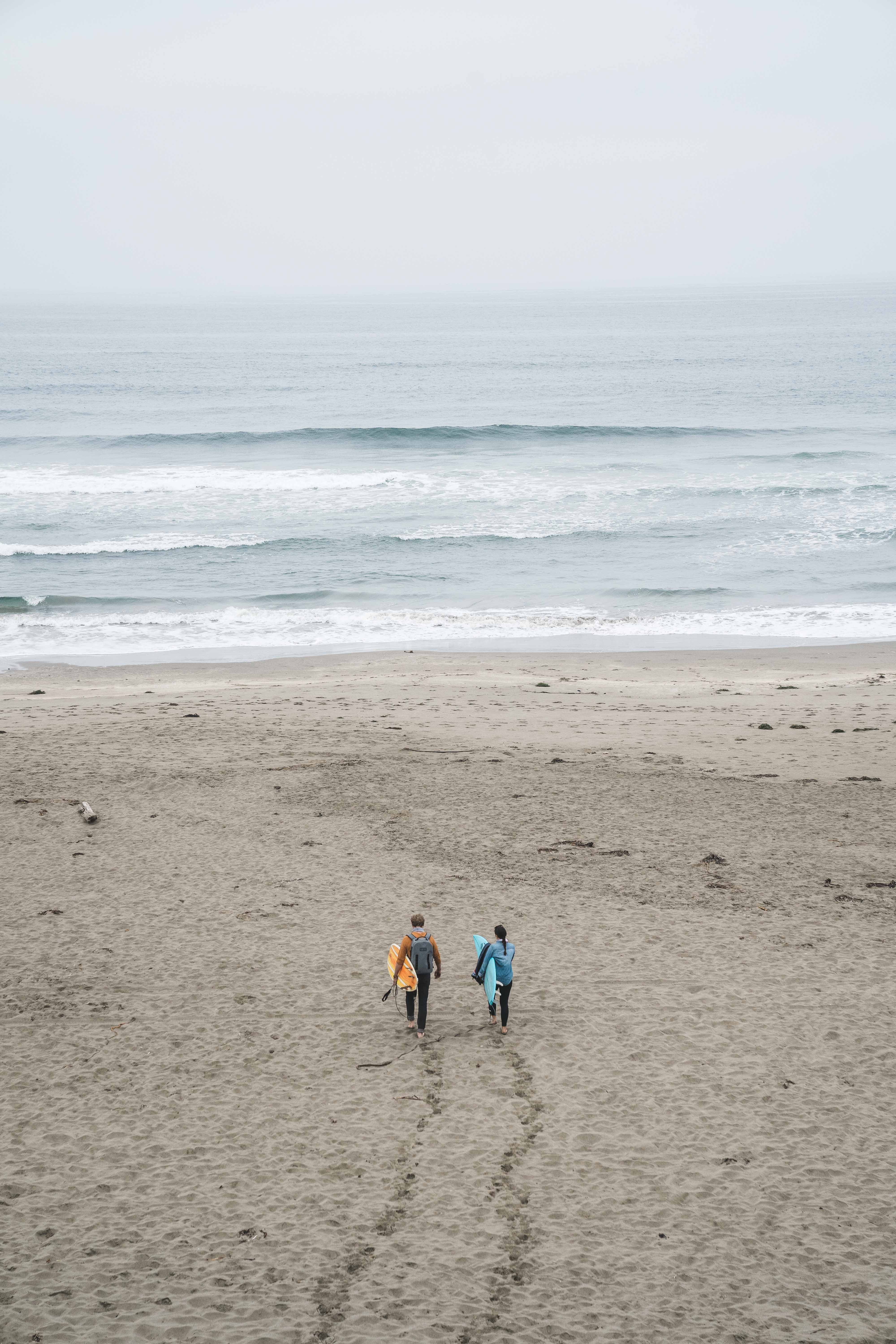 couple arriving at beach surfing