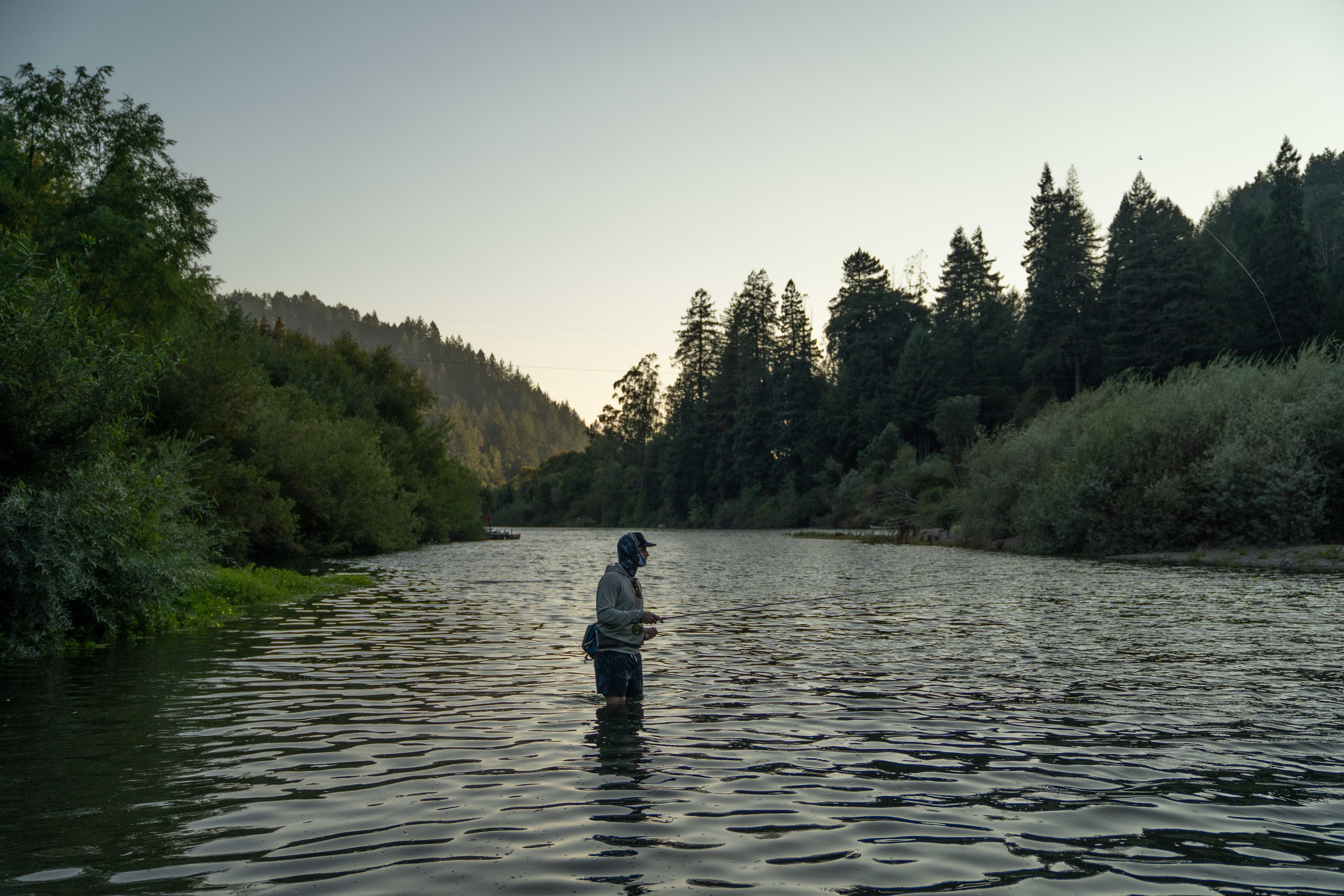 man standing in river fishing at sunset