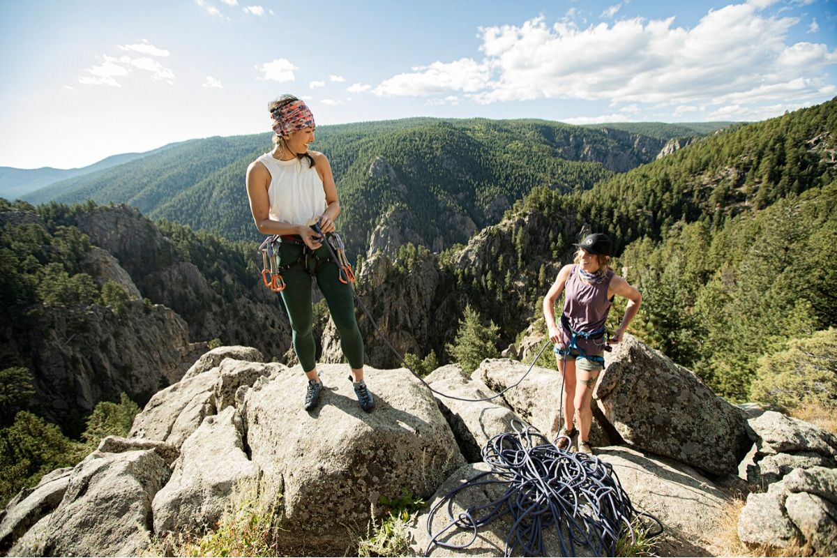 females rock climbing on top of mountain